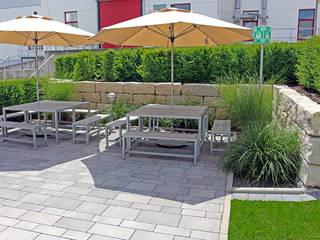 Außenanlage mit Aufenthaltsbereich einer Modernen Lehrlingswerkstatt. RAUCH Gaten- und Landschaftsbau GbR Moderne Bürogebäude Grau
