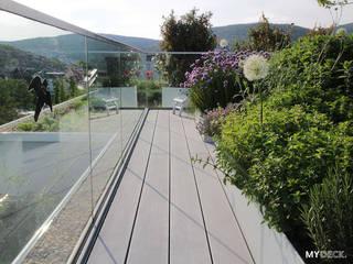 Terrassengestaltung mit WPC Dielen und seitlicher Bepflanzung Moderner Balkon, Veranda & Terrasse von MYDECK GmbH Modern