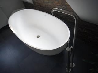 Vrijstaand design bad met luxe VOLA badkraan:   door De Eerste Kamer