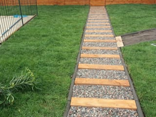 Camino de madera y piedra de río: Antejardines de estilo  por Deck and Garden