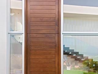 Puerta de ingreso a vivienda. con medidas y proporciones descomunales, junto con las puertas interiores que acompañan el diseño moderno y extraordinario del ingreso. :  de estilo  por Maretich Aberturas de Madera