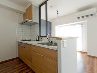 キッチンはクロスが映える様シンプルに: 有限会社グラデンパシフィックが手掛けたです。