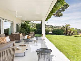 Porche (Salón) / Jardín: Villas de estilo  de Abrils Studio