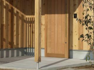 三角屋根の家: ELD INTERIOR PRODUCTSが手掛けた木製ドアです。