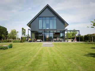 houten woning in de onder architectuur aangelegde tuin:  Houten huis door StrandNL architectuur en interieur