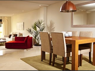 Comedor y salón con mesa de madera y sillas tapizadas de color beige sobre suelo de mármol blanco y sofá rojo que rompe con los colores claros: Comedores de estilo  de AVANTUM