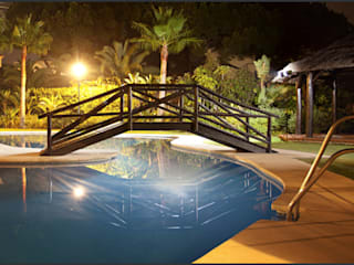 Jardín compuesto con una gran piscina y un puente de madera.: Piscinas de jardín de estilo  de AVANTUM