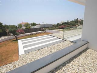 Cobertura da casa vista do 1º andar : Telhados  por OGGOstudioarchitects, unipessoal lda