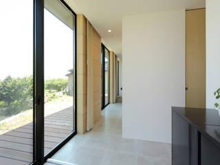 デッキテラスに面した廊下に繋がる玄関: 株式会社建築工房DADAが手掛けた廊下 & 玄関です。,