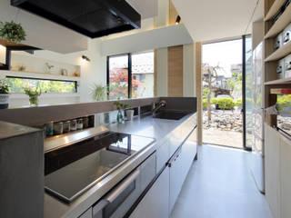 ステンレスとモルタル塗装でシンプルなキッチン: 株式会社建築工房DADAが手掛けたシステムキッチンです。