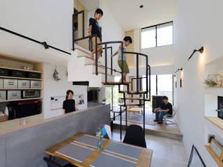 螺旋階段で吹き抜けを緩やかにエリア分け: 株式会社建築工房DADAが手掛けたリビングです。