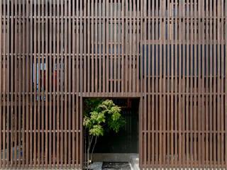 ルーバーの内側に緑がのぞく玄関ポーチ: 株式会社建築工房DADAが手掛けた木造住宅です。