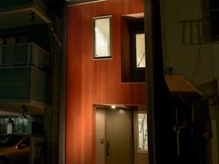 夜の街に浮かび上がるレッドシダーの外壁: ティー・ケー・ワークショップ一級建築士事務所が手掛けた長屋です。