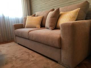 O conforto do sofá: Salas de estar  por Cássia Lignéa