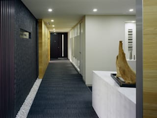 エントランスから大会議室を見る: 松岡淳建築設計事務所が手掛けた廊下 & 玄関です。