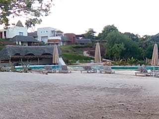 Vista del resort dalla spiaggia: Hotel in stile  di Ing. Massimiliano Lusetti
