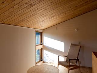田園を望む現代の庵: FAD建築事務所が手掛けた小さな寝室です。