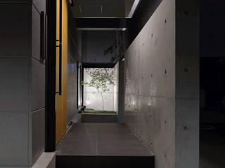 コンクリート壁のエントランス: (株)建築デザイン研究所が手掛けた家です。
