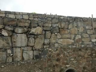 Puente con muro de mampostería.: Paredes de estilo  por Trevalo Urbanizaciones y Construcciones