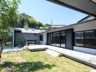 芝生を囲む平屋: 風景のある家.LLCが手掛けた木造住宅です。