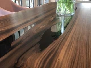 Esstisch mit Glaswangen in Nussbaum aus einer ganzen Stammbohle:   von Bernhard Preis - Interior Design aus der Region Tegernsee