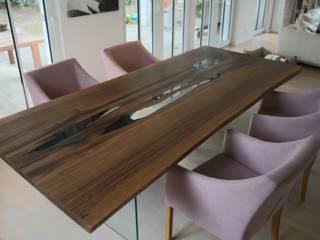 Esstisch mit Glaswangen in Nussbaum aus einer ganzen Stammbohle: modern  von Bernhard Preis - Interior Design aus der Region Tegernsee,Modern