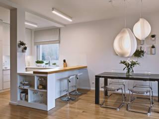Jasna, otwarta kuchnia z widokiem na salon: w bieli i dębie SZARA / studio Nowoczesna jadalnia Drewno O efekcie drewna