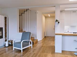 Jasna, otwarta kuchnia z widokiem na salon: w bieli i dębie Nowoczesna jadalnia od SZARA / studio Nowoczesny