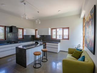 Kitchen with island wrapped around the internal courtyard Modern kitchen by Kamat & Rozario Architecture Modern