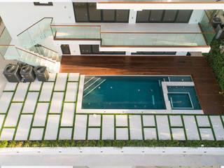 PISCINA, DECK, PLACAS DE CONCRETO E GRAMA ARTIFICIAL Piscinas tropicais por Casa Construções e Reformas Tropical