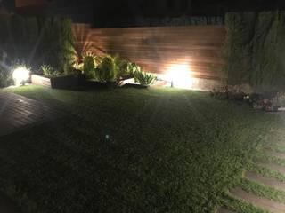 DISEÑO DE JARDIN EN CUARTE DE HUERVA CON TARIMA Y VALLA DE MADERA TROPICAL, JARDINERAS CON PLANTACIONES Y RIEGO. ILUMINACION DE EXTERIOR CON LEDS EMPOTRADOS EN TARIMA TROPICAL IPE, BALIZAS Y PICAS LUMINOSAS EN LA ZONA DE PLANTAS DECORATIVAS Jardines de estilo moderno de Jardín con Clase Moderno