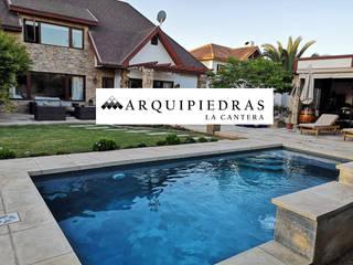 Terraza y borde de piscina de Arquipiedras Rústico