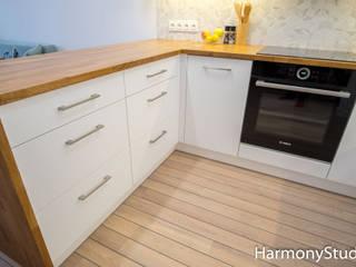 Kuchnia na wymiar z białymi frontami, drewnianymi blatami i półkami od HarmonyStudio Nowoczesny