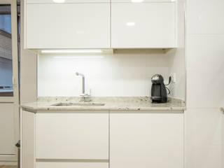 Cocina blanca en L con forma irregular de Suarco Moderno