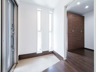 ホワイトとダークブラウンの木目を基調にしたインテリアがおしゃれなシンプルモダンの住宅 株式会社 大岡成光建築事務所 モダンスタイルの 玄関&廊下&階段