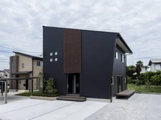 ブラックのガルバリウム鋼板と木目調ルーバーが際立つシンプルモダンなファサードをもつデザインハウス 株式会社 大岡成光建築事務所 モダンな 家