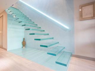 A single-flight cantilever staircase crafted in toughened, laminated glass Railing London Ltd Коридор, прихожая и лестница в модерн стиле