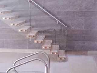 A custom-made floating staircase with oak-clad treads, a clear-glass balustrade and a wall-mounted stainless steel handrail. Railing London Ltd Modern pool