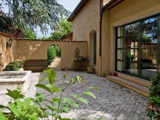 Maison de plain pied avec sol en pierre au design méditerranéen Pierre Bernard Création Balcon, Veranda & Terrasse méditerranéens