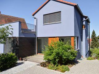 Wohnhaus aus Massivholz am Hang mit Praxis Herrmann Massivholzhaus GmbH Holzhaus Massivholz Lila/Violett