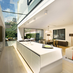 ​Kitchen and sitting area with views of the back garden at Bedford Gardens house. Nash Baker Architects Ltd Modern kitchen Glass White