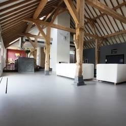 Grijze gietvloer in woonboerderij:  Woonkamer door Motion Gietvloeren