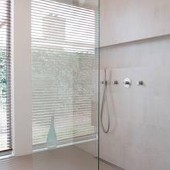 Inloopdouche met zicht op tuin:  Badkamer door Architect2GO