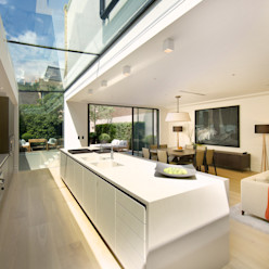 Kitchen and sitting area with views of the back garden at Bedford Gardens house. Nash Baker Architects Ltd Modern kitchen Glass White