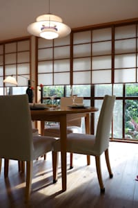 障子とバラの庭が居間に拡張性をあたえ広く見える: T設計室一級建築士事務所/tsekkeiが手掛けたリビングです。