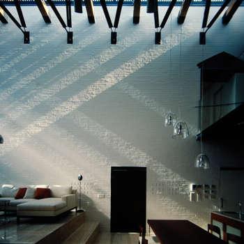 壁に住む家: 合資会社d.n.a.が手掛けたリビングです。