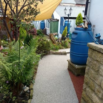 Resin bound paving installed over a concrete path creating more attractive surface.: modern Garden by Permeable Paving Solutions UK