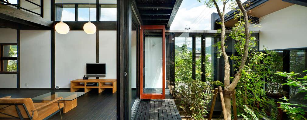 居間と中庭: 石井智子/美建設計事務所が手掛けたリビングです。