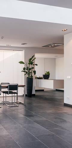 Luxe renovatie met zwevende dakopbouw, maatwerk keuken met zwevend HI-MACS keukenblok en houtfineer kastenwand:  Woonkamer door Joep van Os Architectenbureau