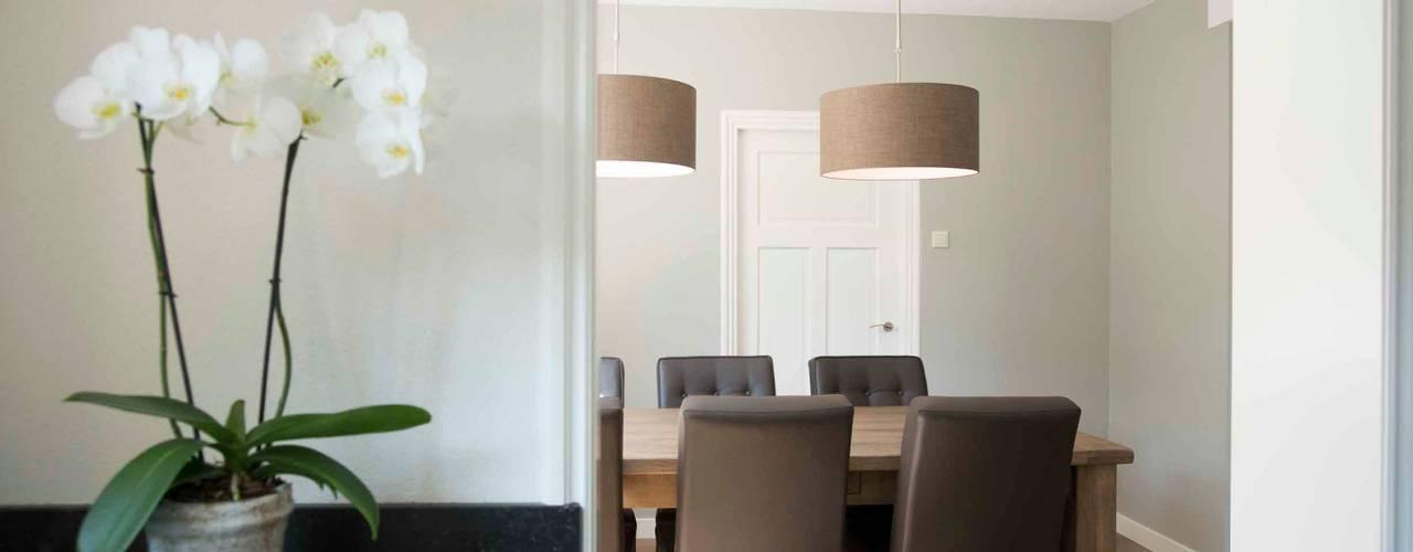Eettafel met gecapitonneerde stoelen en stoffen lampenkappen:  Eetkamer door Hemels Wonen interieuradvies en ontwerp